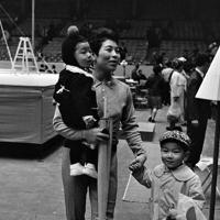 自分の子どもを連れて体操男子の応援にやって来た池田敬子選手。池田選手は個人総合6位。種目別平均台6位=東京・渋谷区の東京体育館で1964年10月18日、鈴木茂雄撮影