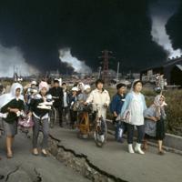 新潟地震で避難する周辺住民。後方は黒煙をあげて燃え続ける石油タンク=新潟市で1964年6月