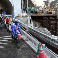 開通した国道413号の崩落箇所を見ながらロードバイクで走る人たち。横山トンネル(奥)付近は当面の間、片側交互通行が続く=相模原市緑区で2019年12月29日、滝川大貴撮影