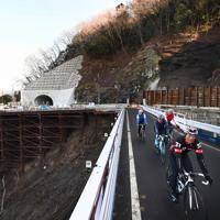 開通した国道413号の崩落箇所を見ながらロードバイクで疾走する人たち。横山トンネル(奥)付近は当面の間片側交互通行が続く=相模原市緑区で2019年12月29日、滝川大貴撮影