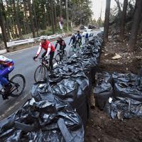 台風による土砂崩落で土のうが積まれた箇所をロードバイクで疾走する人たち=相模原市緑区で2019年12月29日、滝川大貴撮影