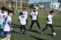 子供たちとサッカーをする松永祥兵選手(右から2人目)=静岡県三島市南二日町で