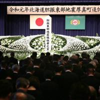 胆振東部地震の追悼式で犠牲者に黙とうする参列者たち=北海道厚真町で、貝塚太一撮影