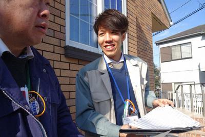固定資産税査定の調査で、先輩職員と書類を確認する千葉県船橋市職員の伊藤純基さん=同市で