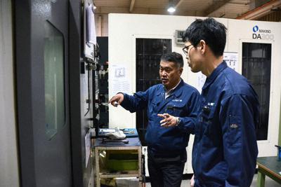 金属を加工する工作機械を前に若手社員を指導する山城機工の岡西栄作社長(左)=神戸市長田区で2019年11月28日、釣田祐喜撮影