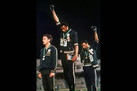 In this Oct. 16, 1968 file photo, U.S. athletes Tommie Smith, center, and John Carlos raise their gloved fists after Smith received the gold and Carlos the bronze for the 200-meter sprint at the Summer Olympic Games in Mexico City. The International Olympic Committee published guidelines, on Jan. 9, 2020 specifying which types of athlete protests will not be allowed at the 2020 Tokyo Games. (AP Photo)