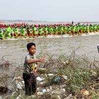 リサイクル業者に売るために、観客や競技者が捨てたアルミ缶とペットボトルを集める少年=カンボジアで2019年11月、フォトジャーナリストの高橋智史さん撮影