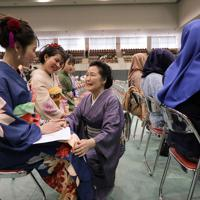 塩釜市の成人式でもうけられた外国人の席に晴れ着を着て座るベトナムやカンボジアの技能実習生たち。約520人が成人した塩釜市は、市内の水産加工会社などで技能実習生として働いている外国人約30人にも、それぞれの母国語で書かれた招待状を送った。希望者には地元の着付け講師の岡沢マキ子さん(81)=中央=たちが「日本で楽しい思い出をつくってほしい」と、無料で晴れ着を着せた。2018年に来日したベトナム・ハノイ市のファム・ティ・フエンさん(20)は初めての着物に「帯を後ろで結んでいるのがきれいでおもしろい。ベトナムには成人式のような催しはないのでうれしい」と話した=宮城県塩釜市で2020年1月12日午後1時19分、和田大典撮影