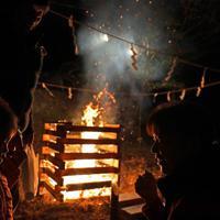 どんと祭の火を囲む宮城県丸森町の耕野地区の住民たち。同地区の住民たち約50人でつくる「やまと七草会」は21年前から1月7日に、集会所前でどんと祭を続けている。同町は昨年の台風19号で甚大な被害を受け、道路や建物の復旧作業が続いている。しめ飾りなどを火に入れ手をあわせた斎藤守雄さん(81)は、毎年どんと祭を行っていた近所の神社が台風の影響で壊れたため、今年はこちらのどんと祭に参加した。「今まで経験したことのない大きな水害で、近所の仲間も亡くなった。地球環境が変わって、また大きな台風が来ることは覚悟しなきゃなんないのかもしれないけど、今年はあんな災害が起きないことを願うほかないですね」と話した=宮城県丸森町で2020年1月7日午後5時17分、和田大典撮影