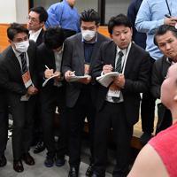 インフルエンザ予防のためマスクを着用して支度部屋で取材する記者ら=東京・両国国技館で2020年1月12日、大西岳彦撮影