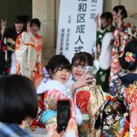 式典会場前で記念撮影する晴れ着姿の新成人たち=名古屋市昭和区で2020年1月12日、兵藤公治撮影