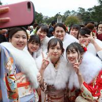 スマートフォンで記念撮影する晴れ着姿の新成人たち=名古屋市昭和区で2020年1月12日、兵藤公治撮影