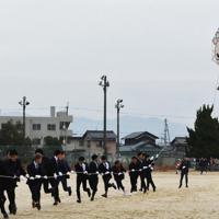 自分たちが作った20畳大凧を揚げる新成人=東近江市聖徳町の聖徳中学校グラウンドで2020年1月12日午後2時10分、蓮見新也撮影