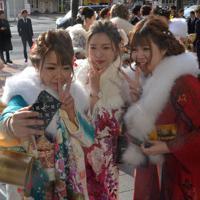 スマートフォンのカメラで撮影する新成人ら=青森市のリンクステーションホール青森で2020年1月12日午前10時35分、井川加菜美撮影