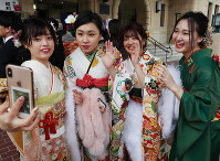 Women clad in kimonos make a video call to a friend, who has gone to study abroad and cannot attend their coming-of-age ceremony, in Nagoya's Showa Ward on Jan. 12, 2020. (Mainichi/Koji Hyodo)