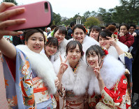 Women clad in kimonos take a selfie during a coming-of-age ceremony in Nagoya's Showa Ward on Jan. 12, 2020. (Mainichi/Koji Hyodo)