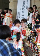Women clad in kimonos take a selfie in front of a signboard during a coming-of-age ceremony in Nagoya's Showa Ward on Jan. 12, 2020. (Mainichi/Koji Hyodo)