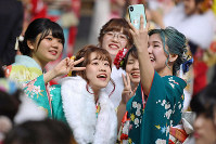 Women clad in kimonos take a selfie during a coming-of-age ceremony in Kitakyushu's Kokurakita Ward on Jan. 12, 2020. (Mainichi/Takashi Kamiiriki)