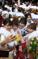 Women clad in kimonos take a selfie during a coming-of-age ceremony in Sapporo's Chuo Ward on Jan. 12, 2020. (Mainichi/Kan Takeuchi)
