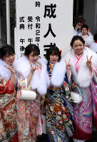 Women clad in kimonos take a selfie in front of a signboard during a coming-of-age ceremony in Sapporo's Chuo Ward on Jan. 12, 2020. (Mainichi/Kan Takeuchi)