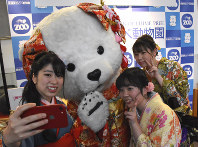 People clad in kimonos and suits take a selfie with a mascot of Peace the polar bear, who turned 20 at Tobe Zoological Park, during a coming-of-age ceremony in the town of Tobe, Ehime Prefecture, on Jan. 12, 2020. (Mainichi/Yuichi Nakagawa)