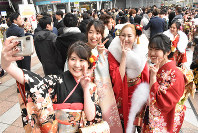 Women clad in kimonos take a selfie during a coming-of-age ceremony at Sunport Hall Takamatsu in the city of Takamatsu, Kagawa Prefecture, on Jan. 12, 2020. (Mainichi/Keiko Yamaguchi)