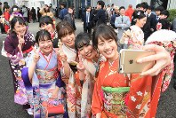 Women clad in kimonos take a selfie outside a venue during a coming-of-age ceremony in the city of Kochi on Jan. 12, 2020. (Mainichi/Yusuke Kori)