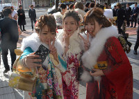 Women clad in kimonos take a selfie during a coming-of-age ceremony at Link Station Hall Aomori in the city of Aomori on Jan. 12, 2020. (Mainichi/Kanami Ikawa)