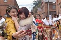 Women clad in kimonos take a selfie during a coming-of-age ceremony at Maizuru Brick Park in the city of Maizuru, Kyoto Prefecture, on Jan. 12, 2020. (Mainichi/Kazuo Namekata)