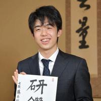 「研鑽(けんさん)」と揮毫(きごう)した色紙を手に笑顔を見せる藤井聡太七段=大阪市北区で昨年12月7日、平川義之撮影
