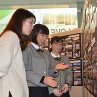 定点観測してきた町の移ろいを来場者に説明する大槌高1年の篠崎愛華さん(中央)と臼沢夏弥さん(右)=神戸市中央区の「人と防災未来センター」で