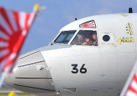 A crew member of a P-3C Maritime Self-Defense Force patrol plane waves to his family on Jan. 11, 2020, before the aircraft departs from Naha Air Base in the city of Naha in the southernmost prefecture of Okinawa to head to Djibouti in Africa ahead of its dispatch to the Middle East. (Mainichi/Noriko Tokuno)