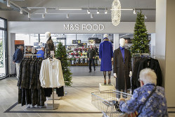 Marks & Spencer Challenges Supermarkets With Big Food Stores Clothing sits on display for sale at Marks and Spencer Group Plc's newly opened store in Fraddon, U.K. on Wednesday, Oct. 23, 2019. Marks & Spencer plans to open more large food stores, shifting away from a strategy of expanding smaller convenience outlets as it prepares for an alliance with online grocer Ocado Group Plc. Photographer: James Beck/Bloomberg