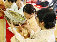 A woman dressed in kimono drinks from a giant tea bowl while being supported by others on both sides, at a special tea ceremony in Saidaiji temple in the city of Nara, western Japan, on Jan. 15, 2020. (Mainichi/Maiko Umeda)