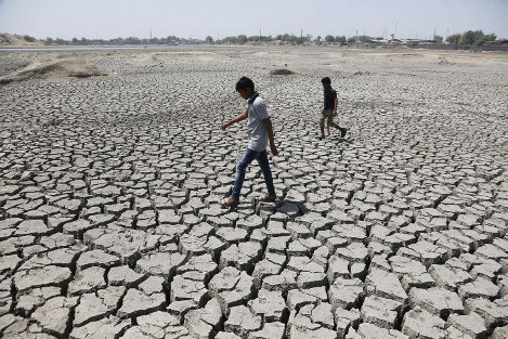 In this May 14, 2016, file photo, boys on their way to play cricket walk through a dried patch of Chandola Lake in Ahmadabad, India. (AP Photo/Ajit Solanki)