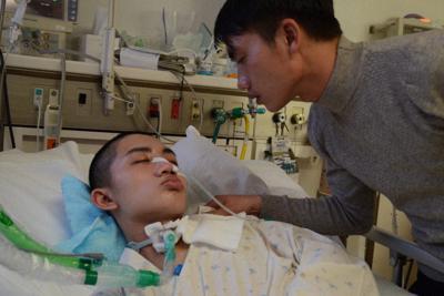 ベッドに横たわったままのトゥさんに名前を何度も呼びかける兄のトゥアンさん=札幌市中央区で