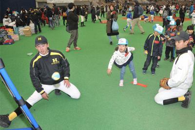 「出雲子ども野球フェスタ」で子供たちにボール投げを教える平田の野球部員(手前左端)