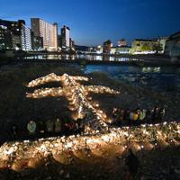 「生」の文字をかたどった石積みの前で黙とうする人たち=兵庫県宝塚市で2020年1月16日午後5時46分、平川義之撮影