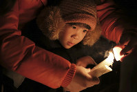 A girl hugged by her father looks at a candle dedicated to the victims of the 1995 Great Hanshin Earthquake in Kobe's Chuo Ward, in western Japan, in the predawn hours on Jan. 17, 2020. (Mainichi/Yohei Koide)
