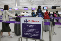 In this March 26, 2019 file photo, passengers wait at the check-in counter of Hong Kong Express Airways at the Hong Kong International Airport. (AP Photo/Kin Cheung)