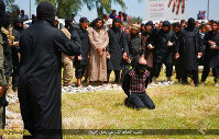 In this photo released on April 27, 2015, by a militant website, which has been verified and is consistent with other AP reporting, Islamic State militants gather around a man, center, knees on the ground, as they prepare to execute him, in Mosul city, north Iraq. (Militant website via AP)