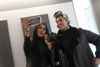 In this Dec. 19, 2019 photo, Amani Al-Khatahtbeh, left, films a video with Maryam Saad after recording a podcast pilot at Spotify's headquarters in New York. (AP Photo/Emily Leshner)