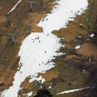 人工降雪機により造られたコース以外、斜面がむき出しになった「リステルスキーファンタジア」のゲレンデ。県外から訪れた中学生らがスキーを練習していた=福島県猪苗代町で2020年1月13日、本社ヘリから手塚耕一郎撮影