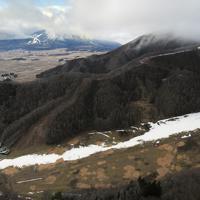人工降雪機により造られたコース以外、全く雪が無いリステルスキーファンタジアのゲレンデ(手前)。左奥に見えるのは、猪苗代スキー場のゲレンデ=福島県猪苗代町で2020年1月13日午後2時40分、本社ヘリから手塚耕一郎撮影