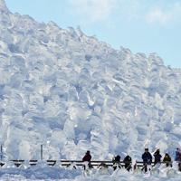 吹雪にさらされて巨大に育った樹氷を楽しむ観光客ら=山形市の蔵王山で2016年2月8日、藤井達也撮影