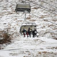 年末のオープンを延期し、1月11日にオープンした星野リゾートアルツ磐梯。ゲレンデ下部には雪がほとんど無く、標高の高いゲレンデで滑り、リフトで下ってきたスノーボーダーら=福島県磐梯町で2020年1月15日、手塚耕一郎撮影