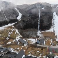 1月11日にオープンした星野リゾートアルツ磐梯。ゲレンデ下部では地肌がむき出しになっている=福島県磐梯町で2020年1月13日、本社ヘリから手塚耕一郎撮影