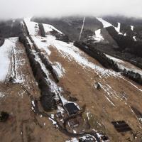 雪不足でゲレンデの地肌がむき出しになっている猪苗代スキー場。オープンが延期されていたが、上部のゲレンデは1月17日にオープンした=福島県猪苗代町で2020年1月13日、本社ヘリから手塚耕一郎撮影