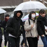 雪が降る中、センター試験の会場に向かう受験生ら=東京都八王子市で2020年1月18日午前8時54分、佐々木順一撮影
