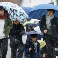 雪が降る中、センター試験の会場に向かう受験生ら=東京都八王子市で2020年1月18日午前9時36分、佐々木順一撮影